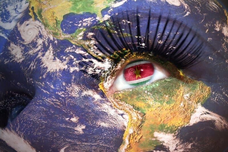 Cara del ` s de la mujer con textura de la tierra del planeta y bandera surinamesa dentro del ojo fotos de archivo libres de regalías