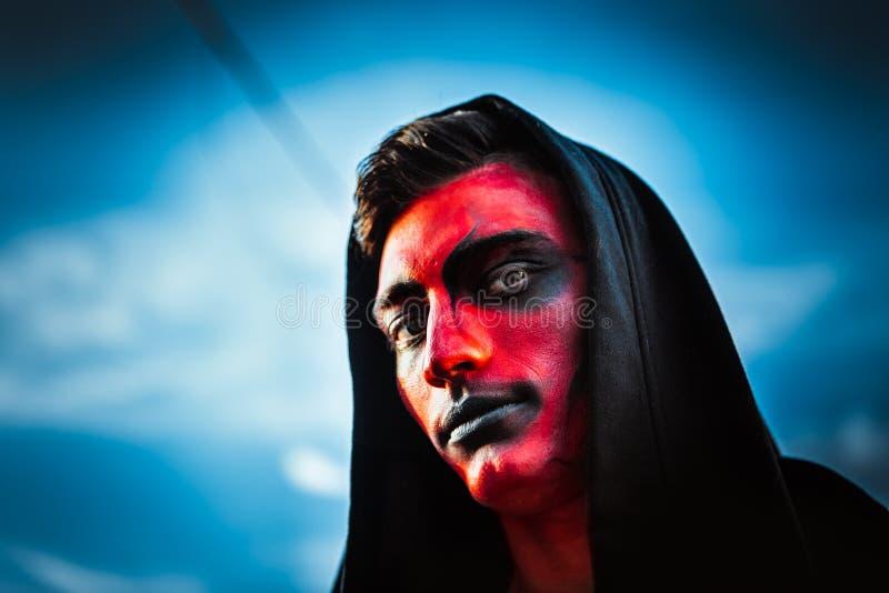 Cara demoníaca roja de un hombre contra el cielo fotografía de archivo