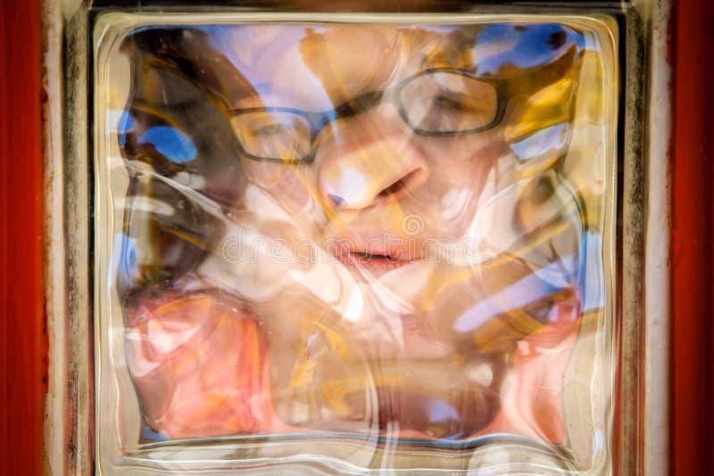 Cara distorcida da menina através do bloco de vidro fotografia de stock