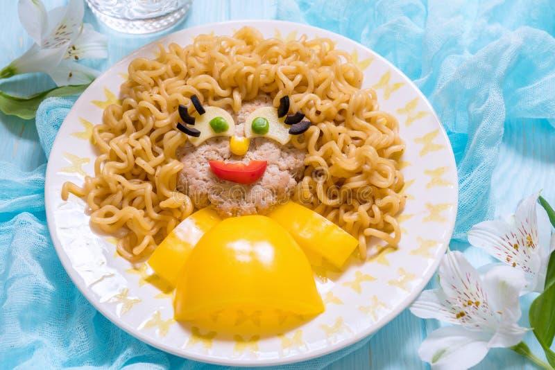Cara divertida de la comida de la muchacha con los tallarines de la chuleta, de las pastas y las verduras fotos de archivo
