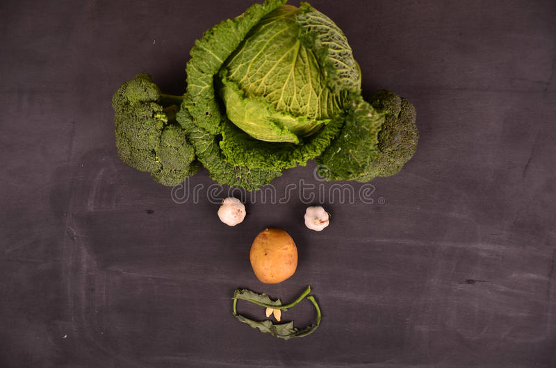 Cara divertida de verduras en la tierra negra imagenes de archivo