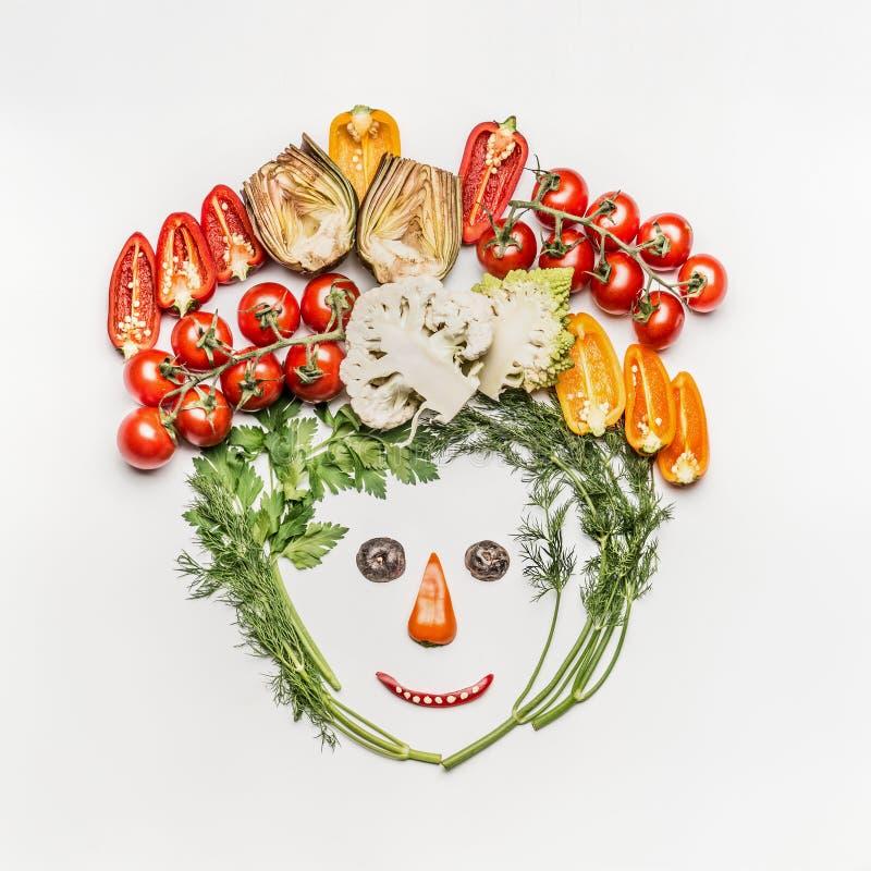 Cara divertida hecha de diversas verduras frescas en el fondo blanco, visión superior foto de archivo