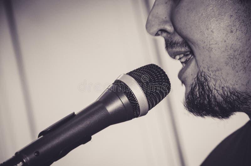 Cara do close-up do cantor com microfone e do canto no fundo preto e branco foto de stock royalty free