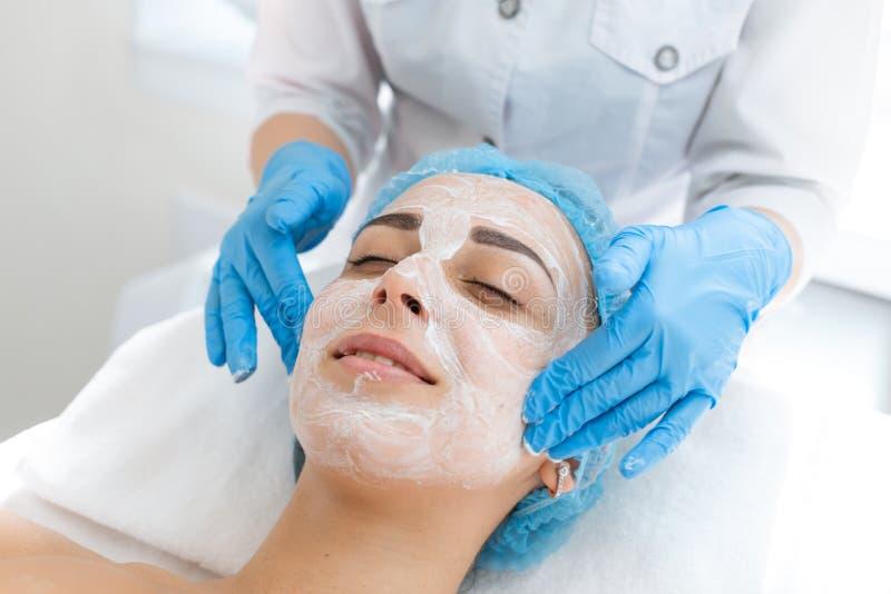 A cara do close-up da moça relaxa e obtém o prazer da massagem facial Hidratando, limpando e cuidados com a pele faciais cosm?tic fotografia de stock royalty free