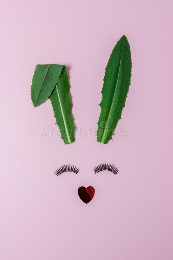 Cara do coelho feita das folhas verdes naturais com as pestanas no fundo cor-de-rosa pastel Conceito mínimo da Páscoa Configuraçã fotografia de stock