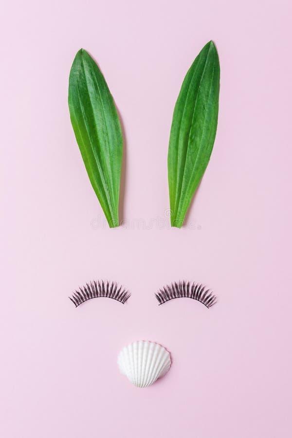 Cara do coelho feita das folhas verdes naturais com as pestanas no fundo cor-de-rosa pastel Conceito mínimo da Páscoa Configuraçã imagem de stock