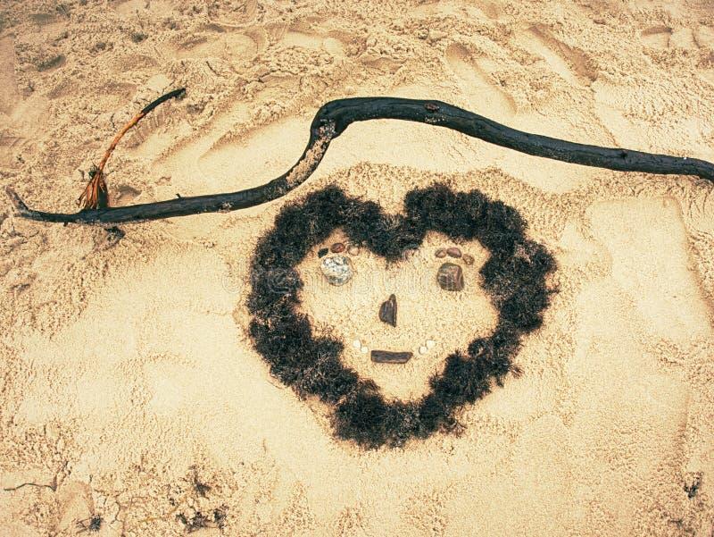 Cara do coração criada na areia na praia foto de stock
