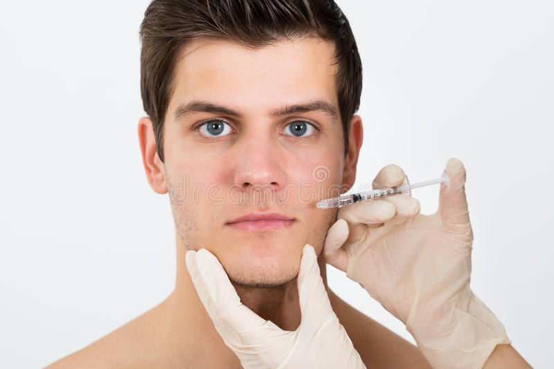 Cara do homem de Person Hands Injecting Syringe On fotos de stock royalty free