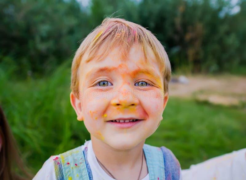 Cara do menino louro pequeno engraçado pintado em pinturas coloridas Retrato do close up fotos de stock royalty free