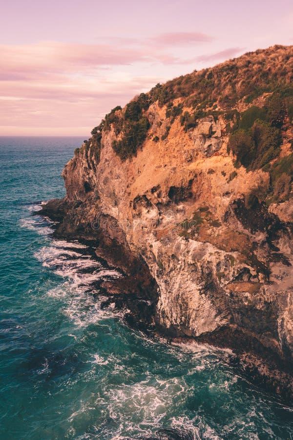 Cara do penhasco com as ondas de água deixando de funcionar com o céu nebuloso do por do sol foto de stock royalty free