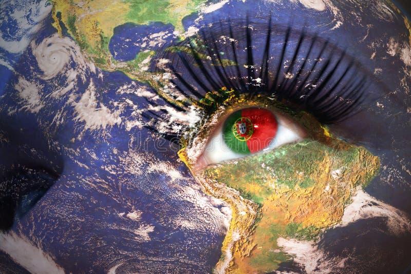 Cara do ` s da mulher com textura da terra do planeta e bandeira portuguesa dentro do olho imagem de stock