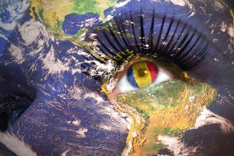 Cara do ` s da mulher com textura da terra do planeta e bandeira romena dentro do olho fotografia de stock royalty free