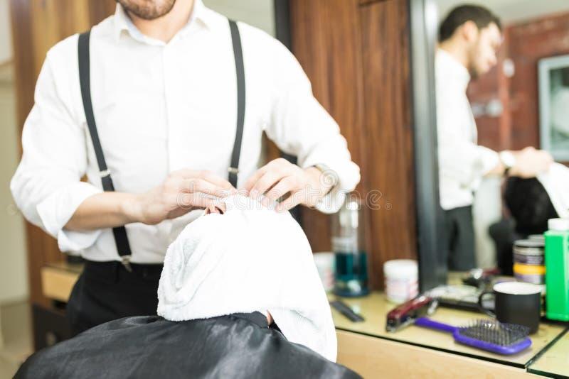 Cara do ` s de Barber Massaging Client após ter aplicado a toalha quente fotos de stock royalty free