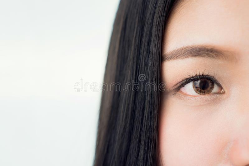 A cara e o olho de uma mulher com boa saúde da pele e os bordos cor-de-rosa Os olhos estão olhando para a frente foto de stock royalty free
