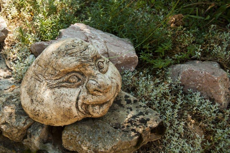 Cara engraçada entre pedras e grama Escultura do jardim Jardim japon?s foto de stock