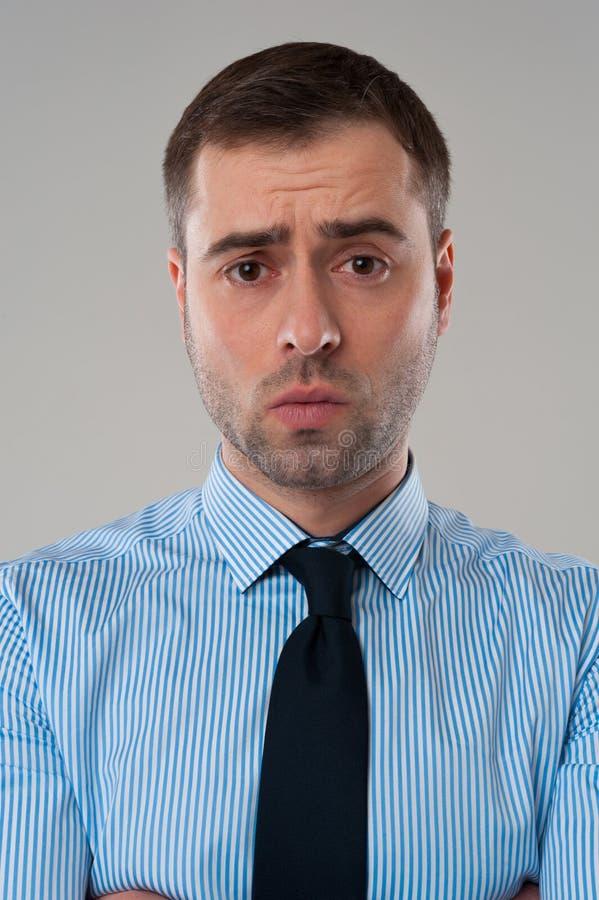 Cara enojada del hombre de negocios en fondo gris fotografía de archivo