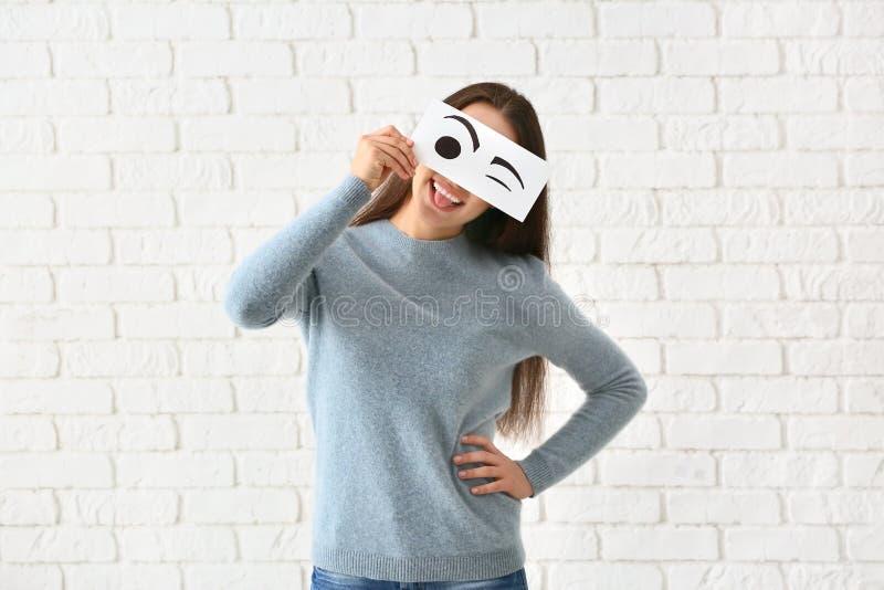 Cara escondendo da jovem mulher emocional atrás da folha de papel com os olhos tirados contra a parede de tijolo branca imagem de stock