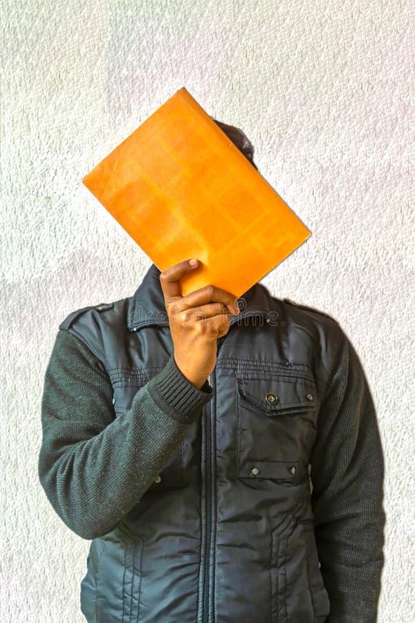 Cara escondendo do homem atrás do livro Em um fundo textured branco imagens de stock