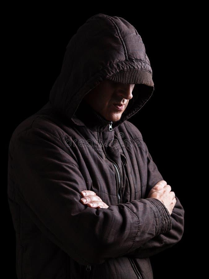 A cara escondendo do homem só, deprimida e frágil, arma-se cruzado e estando na escuridão foto de stock