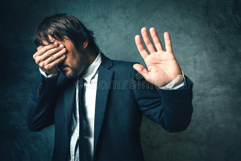 Cara escondendo do político curvado dos fotógrafo após o politica imagens de stock royalty free