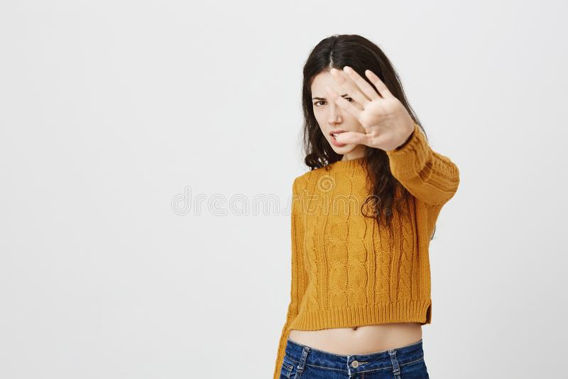 Cara europea joven irritada de la cubierta de la celebridad con la mano estirada, expresando repugnancia y la aversión mientras q imagen de archivo libre de regalías