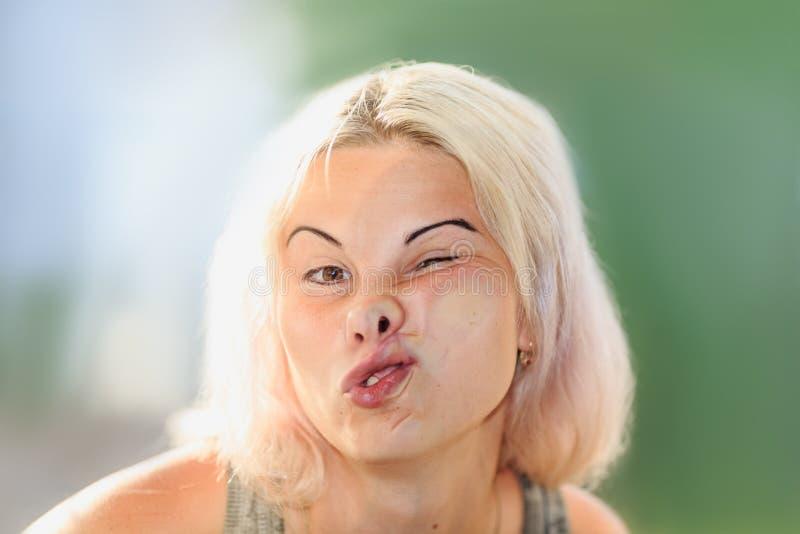 Cara fêmea pressionada contra o vidro ou a janela foto de stock
