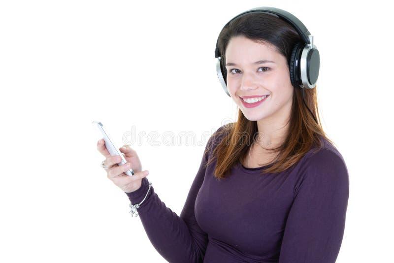 Cara feliz do modelo moreno bonito da menina no telefone celular que olha a música de escuta nos fones de ouvido que estão contra fotos de stock
