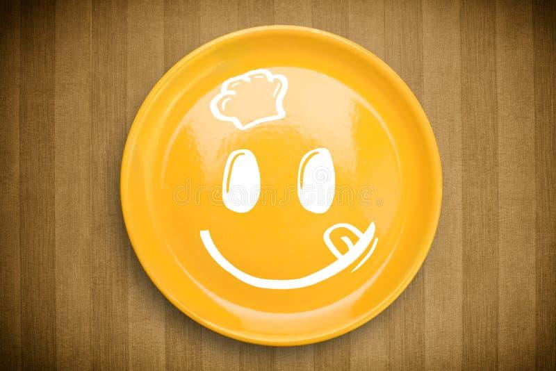 Cara feliz dos desenhos animados do smiley na placa colorida do prato imagem de stock