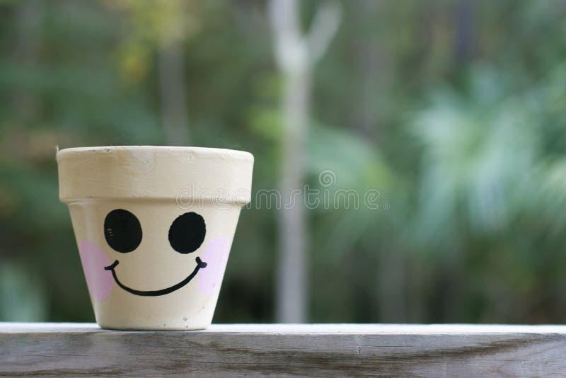 Cara feliz em um potenciômetro de flor fotos de stock royalty free