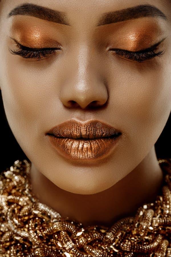 Cara femenina étnica africana de la mujer negra de lujo de la piel del oro Modelo afroamericano joven con joyería imagen de archivo libre de regalías