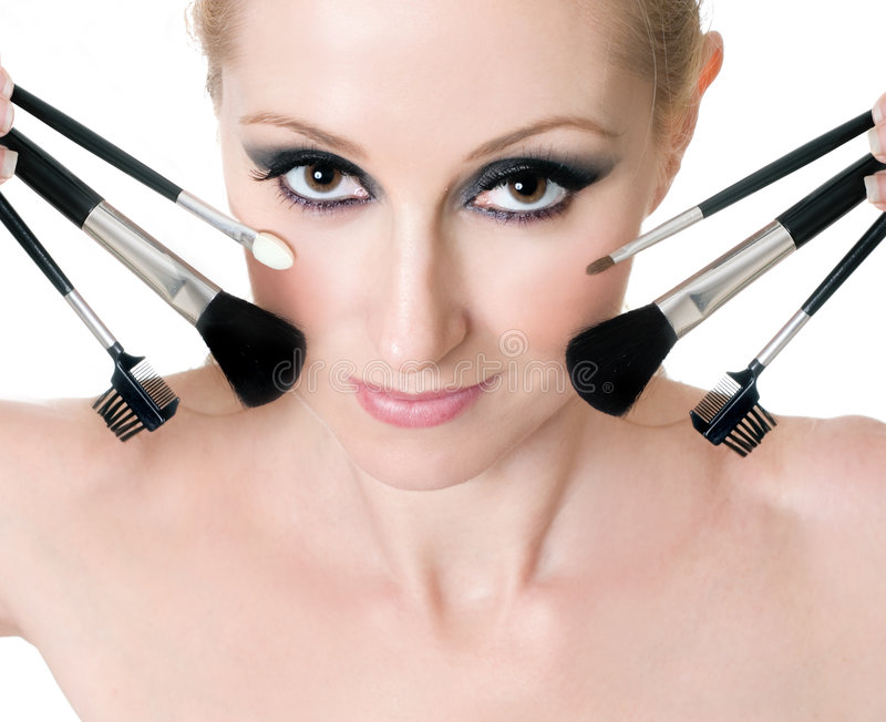 Cara femenina con los cepillos cosméticos del maquillaje foto de archivo libre de regalías
