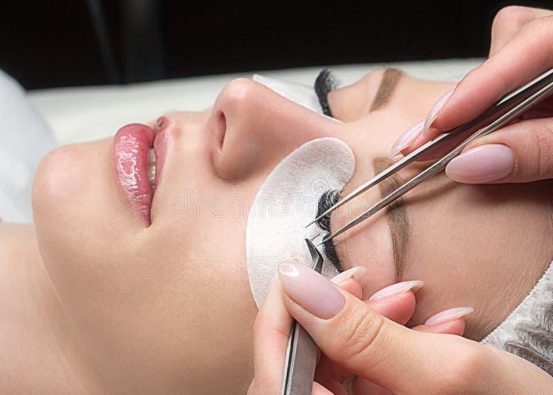 Cara femenina con los latigazos falsos y fingeres de los expertos con las pinzas, procedimiento de la extensión de la pestaña, ci imagen de archivo
