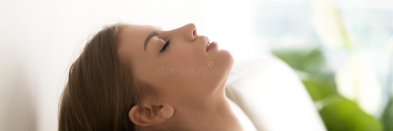Cara femenina de la vista lateral con los ojos cerrados que descansan sobre el sofá imagenes de archivo
