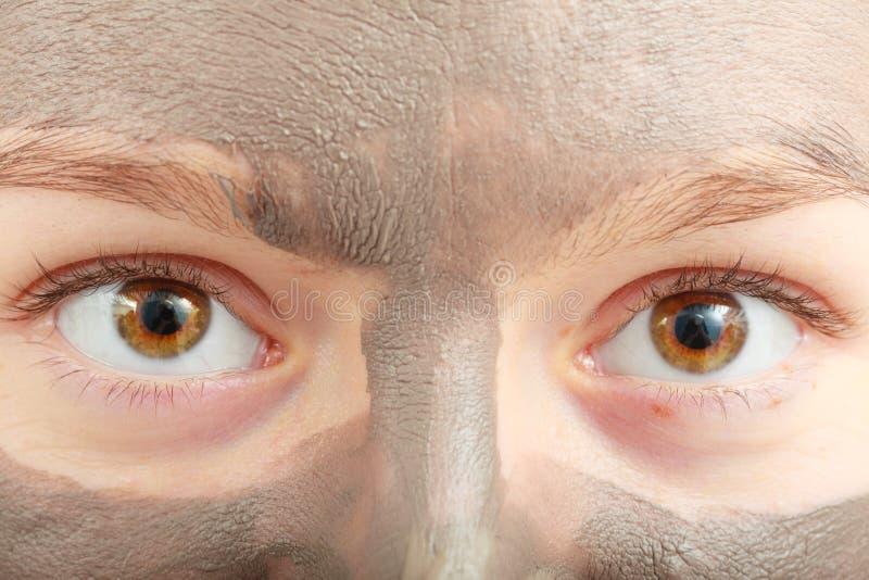 Cara femenina del primer con la máscara facial del fango de la arcilla imagen de archivo