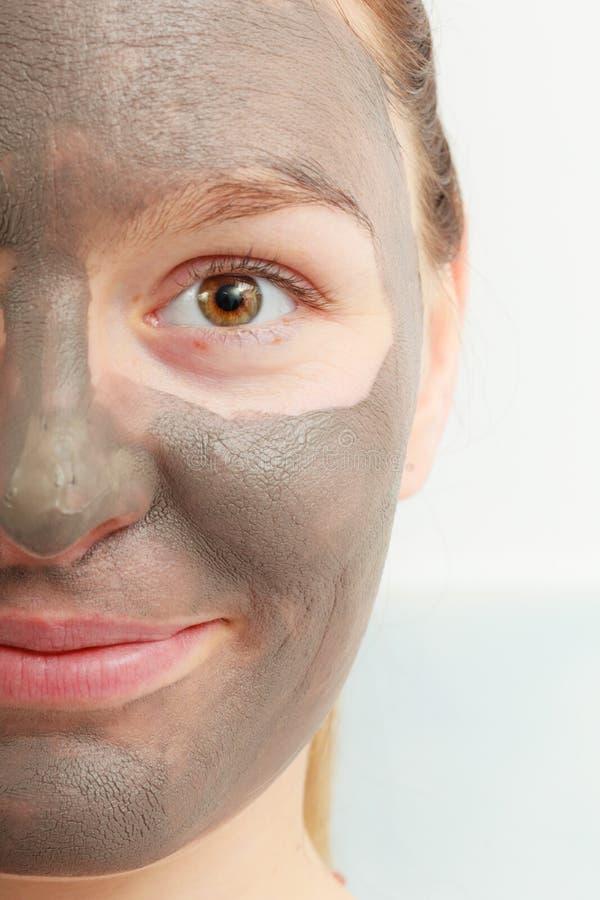 Cara femenina del primer con la máscara facial del fango de la arcilla imagenes de archivo