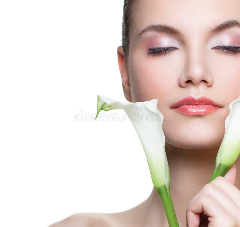 Cara femenina joven La mujer bonita con la flor blanca aislada en el fondo blanco, se cierra encima del retrato imagenes de archivo
