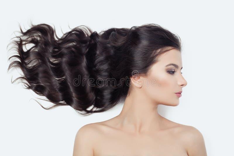 Cara femenina perfecta joven en blanco Mujer linda con soplar el pelo rizado, perfil fotografía de archivo