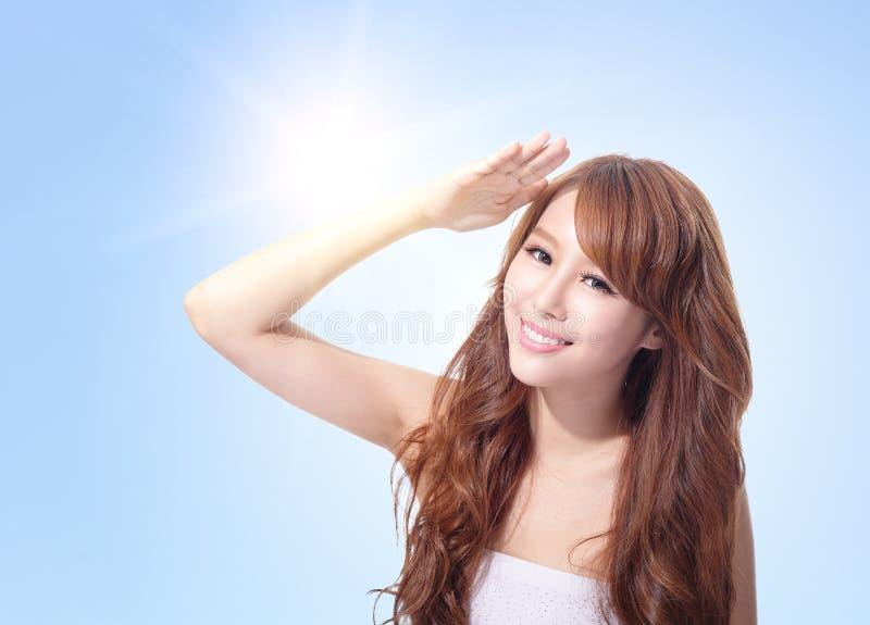 Cara hermosa de la mujer con sol y el cielo imagenes de archivo