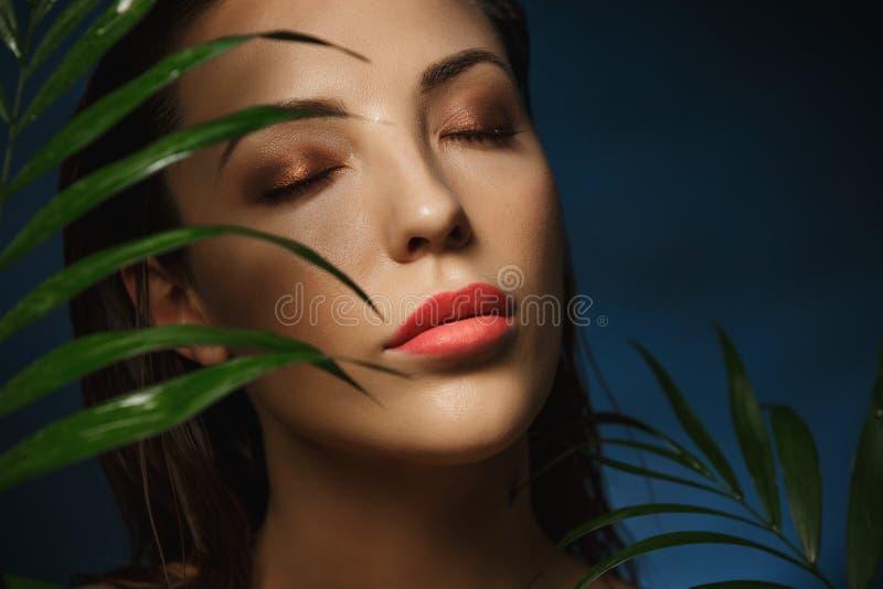 Cara hermosa de la mujer debajo de las hojas verdes exóticas Fotografía de la manera imagen de archivo libre de regalías