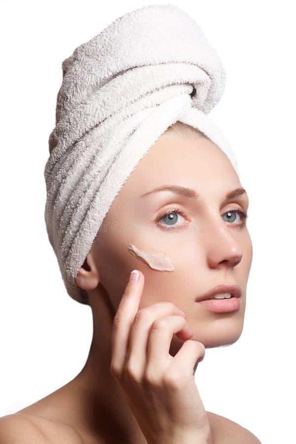 Cara hermosa de la mujer joven con crema cosmética en una mejilla Concepto del cuidado de piel Retrato del primer aislado en blan fotografía de archivo libre de regalías