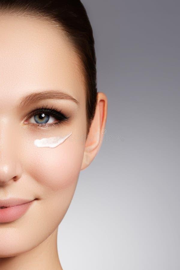Cara hermosa de la mujer joven con crema cosmética en una mejilla SK foto de archivo
