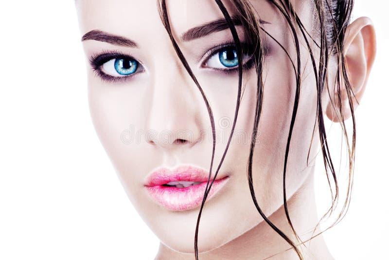 Cara hermosa de una mujer con los ojos azules brillantes fotografía de archivo