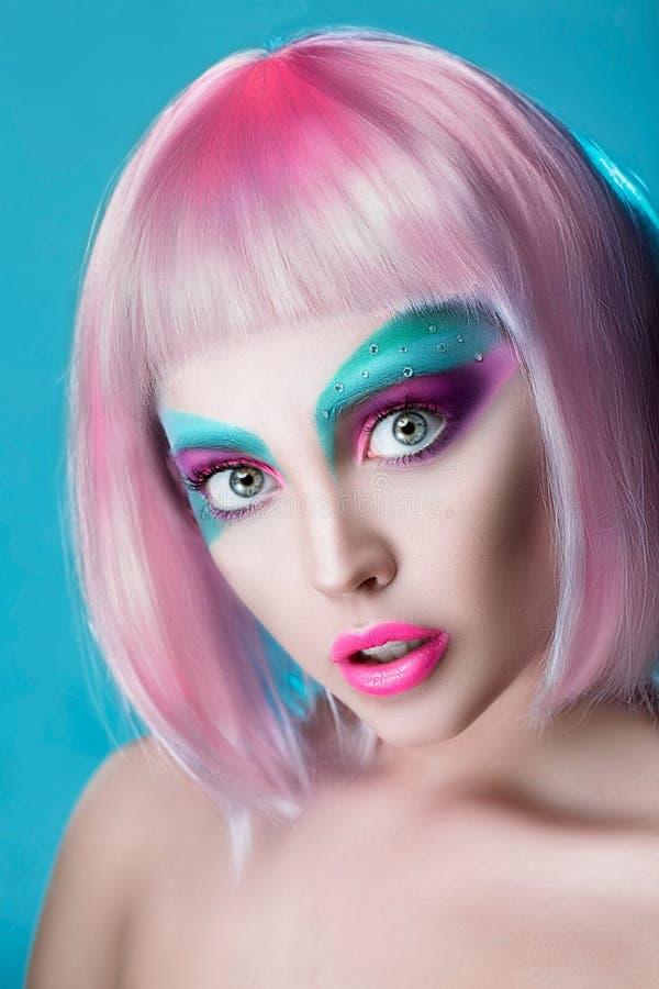 Cara hermosa del primer de la muchacha de la marioneta con arte de la cara en peluca rosada imagen de archivo