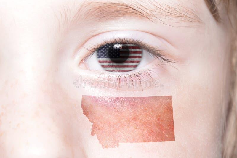 A cara humana do ` s com a bandeira nacional de Estados Unidos da América e montana indicam o mapa imagem de stock