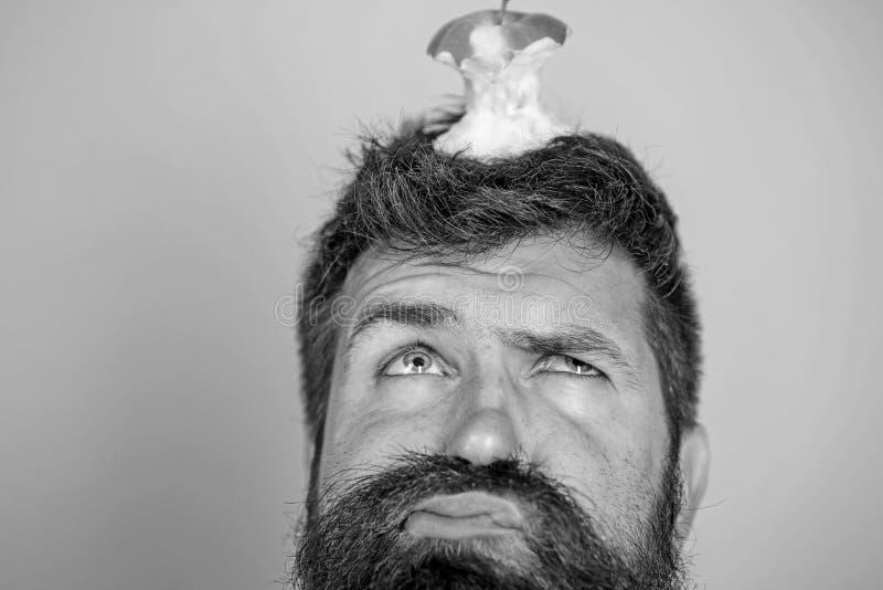 Cara infeliz del inconformista con la blanco del tocón de la manzana en el fondo azul principal, cierre para arriba Barba larga d foto de archivo