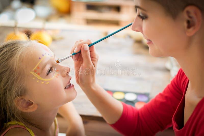 Cara joven de las hijas de la pintura de la madre para el partido de Halloween Halloween o fondo de la forma de vida de la famili fotografía de archivo