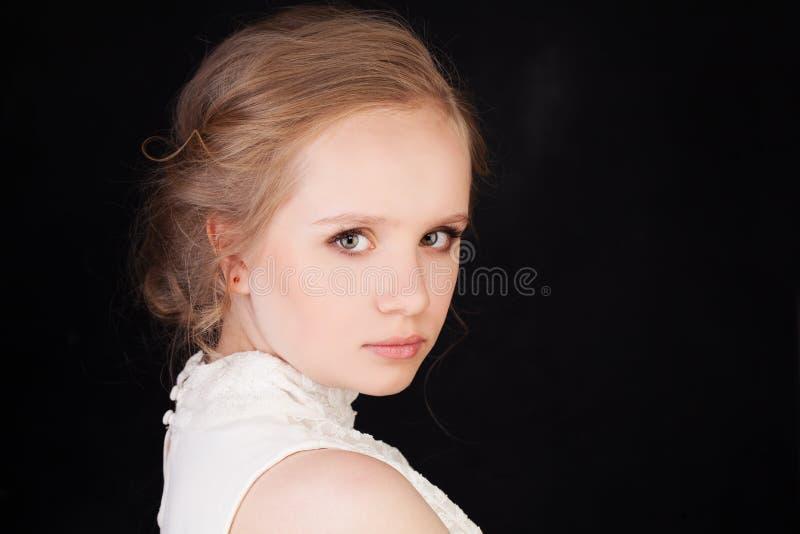 Cara joven Muchacha linda con el pelo rubio en negro foto de archivo libre de regalías