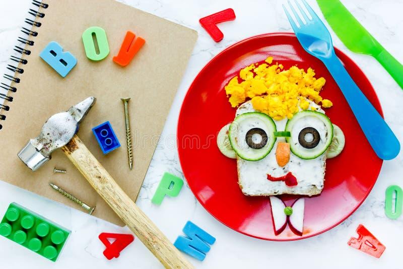 Cara linda formada bocadillo del muchacho de la ensalada del huevo foto de archivo libre de regalías