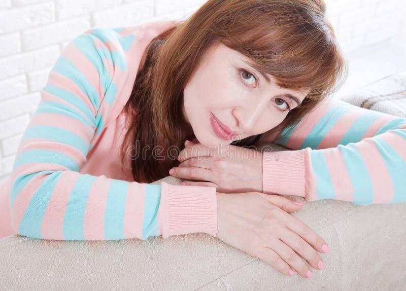 Cara macra de la mujer Retrato del fondo sonriente de la mujer de la Edad Media en casa menopausia Foco selectivo Tiempo del día  fotos de archivo