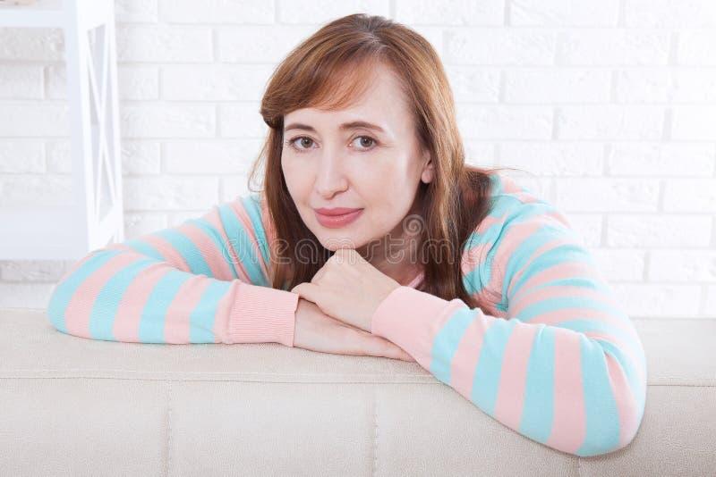 Cara macra de la mujer Retrato del fondo sonriente de la mujer de la Edad Media en casa menopausia Foco selectivo Tiempo del día  foto de archivo libre de regalías
